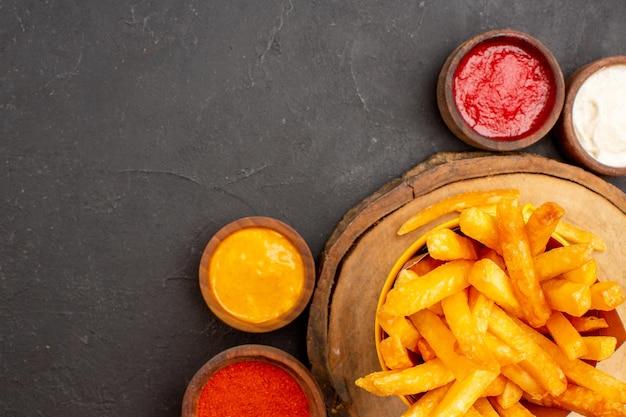 Vista de cima de perto saborosas batatas fritas com molhos no espaço escuro