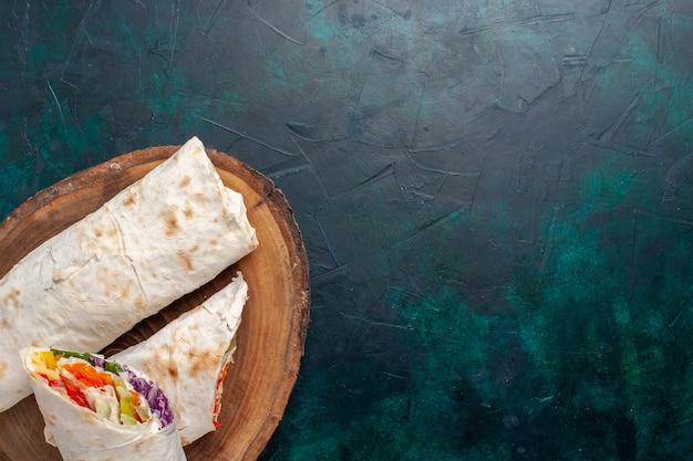 Vista de cima de perto sanduíche de carne um sanduíche feito de carne grelhada no espeto com vegetais em uma mesa azul escura