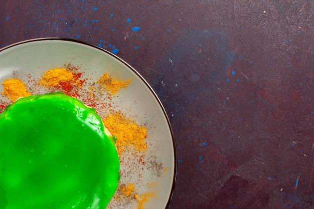 Vista de cima, de perto, um pequeno bolo delicioso com creme verde dentro do prato na superfície escura