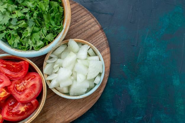 Vista de cima de perto vegetais frescos fatiados, tomates e cebolas com verduras em um prato azul-escuro de mesa comida jantar prato de vegetais