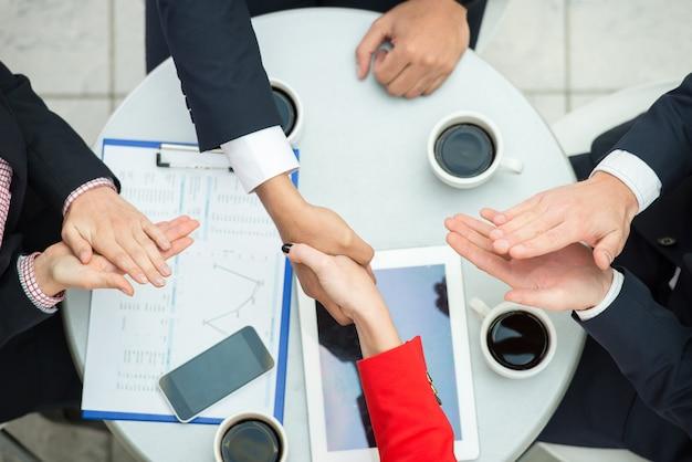 Vista de cima de pessoas de negócios estão apertando as mãos.