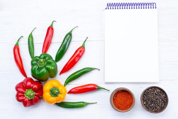Vista de cima de pimentões cheios de pimentas com temperos de bloco de notas de pimentas picantes na mesa branca, produto de ingrediente de comida quente de especiarias vegetais