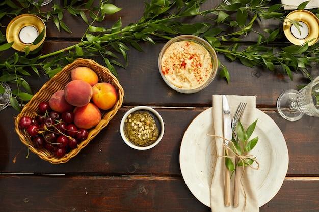 Vista de cima de pratos coloridos de verão na mesa de jantar de madeira decorada com folhas frescas e elementos florais durante a festa ao ar livre