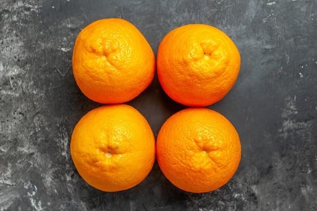 Vista de cima de quatro laranjas frescas orgânicas naturais alinhadas em duas fileiras em fundo escuro