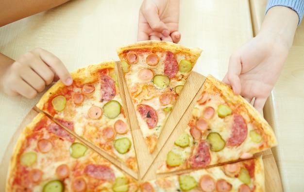Vista de cima de rapazes agarrando uma fatia de pizza