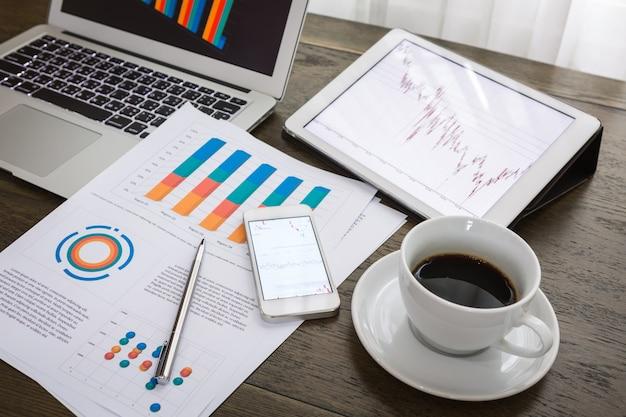 Vista de cima de relatórios financeiros ao lado de uma chávena de café