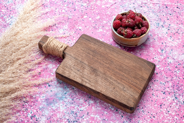 Vista de cima de saborosas framboesas frescas dentro de um prato branco na superfície rosa