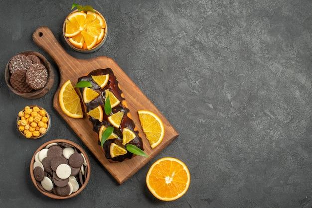 Vista de cima de saborosos bolos, corte de laranjas com biscoitos na tábua de cortar na mesa escura