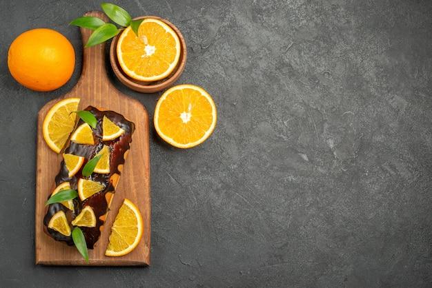 Vista de cima de saborosos bolos inteiros e laranjas cortadas na tábua de cortar na mesa preta