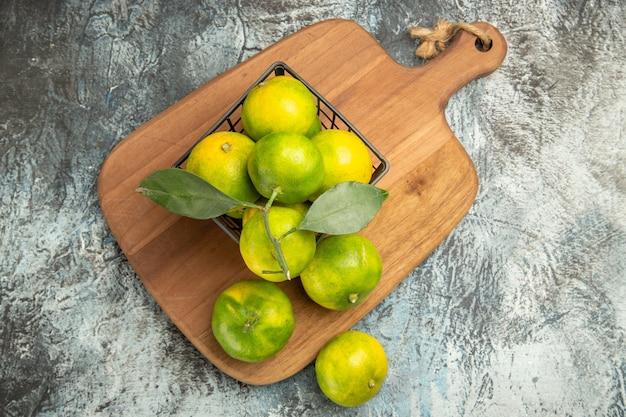 Vista de cima de tangerinas verdes com folhas dentro e fora de uma cesta na tábua de madeira na mesa cinza