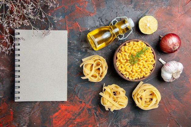 Vista de cima de três porções de macarrão de espaguete e borboleta crus em uma tigela marrom e uma garrafa de óleo de alho e limão com cebola verde ao lado do caderno na mesa de cores misturadas