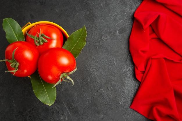 Vista de cima de um balde com tomates e folhas de louro na toalha vermelha em solo escuro