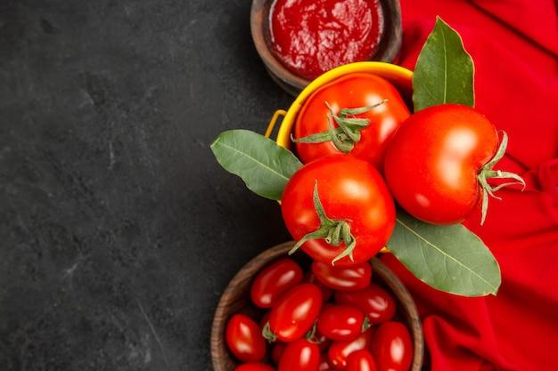 Vista de cima de um balde com tomates e folhas de louro tigelas com tomate cereja e ketchup e toalha vermelha em solo escuro