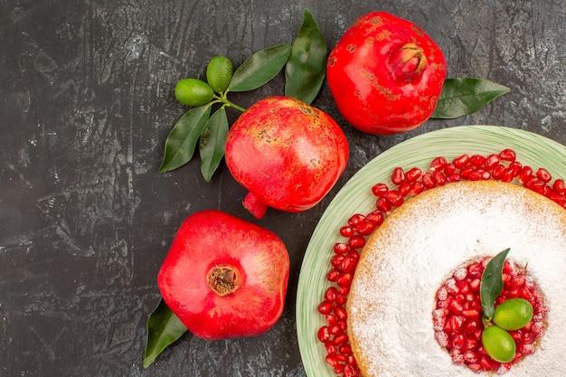 Vista de cima de um bolo com romã um prato de bolo com romã e três romãs