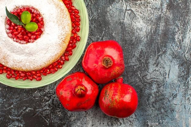 Vista de cima de um bolo com romã, um prato de um bolo apetitoso e três romãs