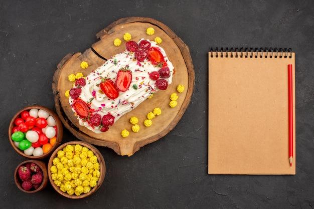 Vista de cima de um bolo cremoso gostoso com frutas e doces no chão preto.