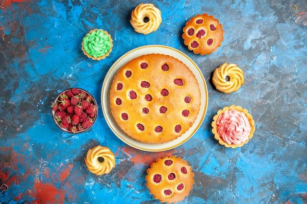 Vista de cima de um bolo de framboesa em um prato oval rodeado por biscoitos de uma tigela de tortinhas com framboesas na superfície azul