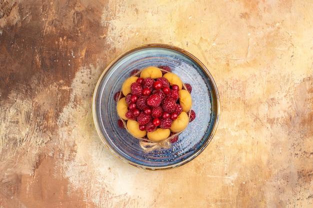 Vista de cima de um bolo de presente recém-assado com frutas na mesa de cores misturadas