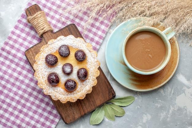 Vista de cima de um bolo delicioso com café com leite em uma mesa leve, bolo doce, açúcar, biscoito