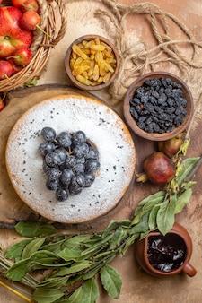 Vista de cima de um bolo um bolo com uvas na cesta de mesa de corte de maçãs e passas