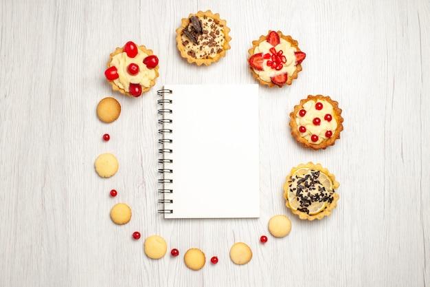 Vista de cima de um caderno cercado de tortas e biscoitos no centro do chão de madeira branco