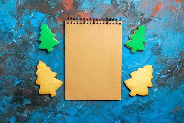 Vista de cima de um caderno de biscoitos da árvore de natal na superfície azul vermelha