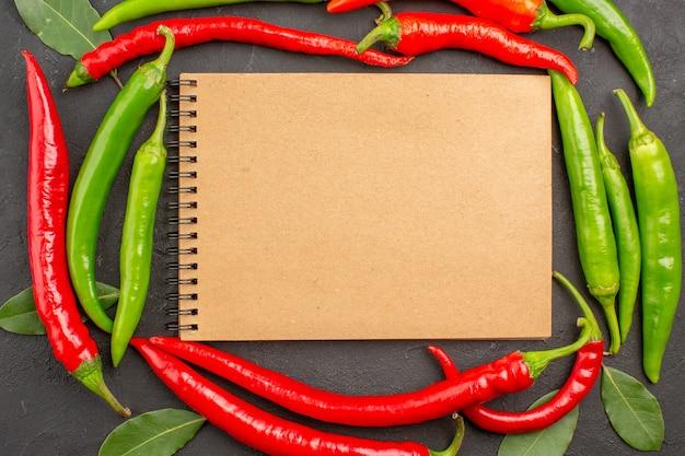 Vista de cima de um caderno no círculo de pimentas vermelhas e verdes e folhas de pagamento em fundo preto