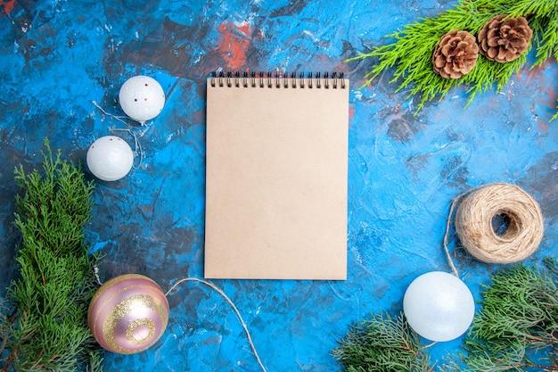 Vista de cima de um caderno pinheiro galho cones palha fio bolas de árvore de natal em fundo azul-vermelho