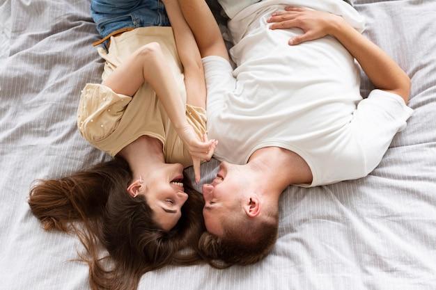 Vista de cima de um casal deitado na cama