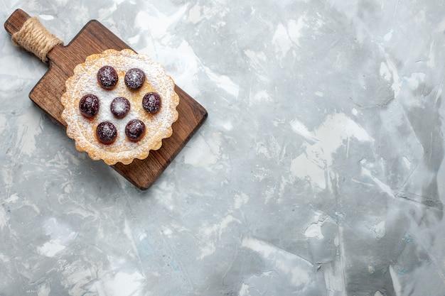Vista de cima de um delicioso bolo com cerejas em uma mesa leve, bolo doce, açúcar, biscoito