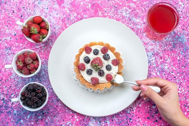 Vista de cima de um delicioso bolo cremoso com diferentes sucos de frutas frescas na luz brilhante, frutas frescas de frutas vermelhas