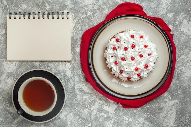 Vista de cima de um delicioso bolo cremoso decorado com frutas em uma toalha vermelha e uma xícara de chá preto ao lado do caderno no fundo de gelo