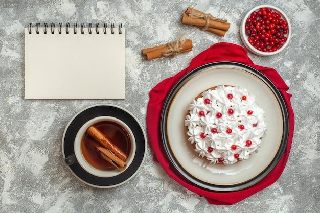 Vista de cima de um delicioso bolo cremoso decorado com frutas em uma toalha vermelha e uma xícara de chá preto