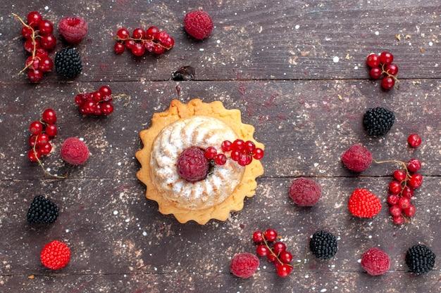 Vista de cima de um delicioso bolo de açúcar em pó junto com diferentes frutas espalhadas por toda a mesa marrom, biscoito de creme de frutas de baga