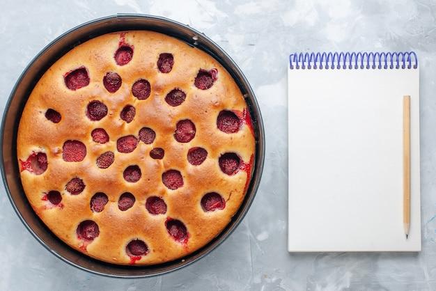 Vista de cima de um delicioso bolo de morango assado com morangos vermelhos frescos dentro com uma panela e um bloco de notas na luz, bolo de biscoito de frutas doce assar