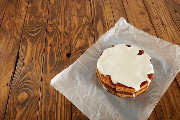 Vista de cima de um delicioso bolo marrom com creme branco por cima deitado na linda mesa de madeira