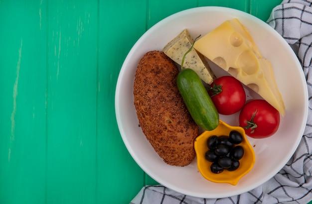 Vista de cima de um delicioso hambúrguer de gergelim em um prato branco com queijo de legumes frescos e azeitonas em um fundo verde de madeira com espaço de cópia
