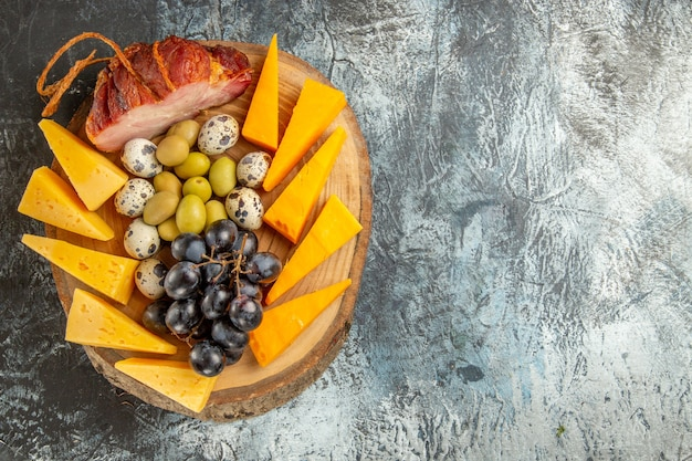 Vista de cima de um delicioso lanche, incluindo frutas e alimentos para vinho em uma bandeja marrom em fundo cinza