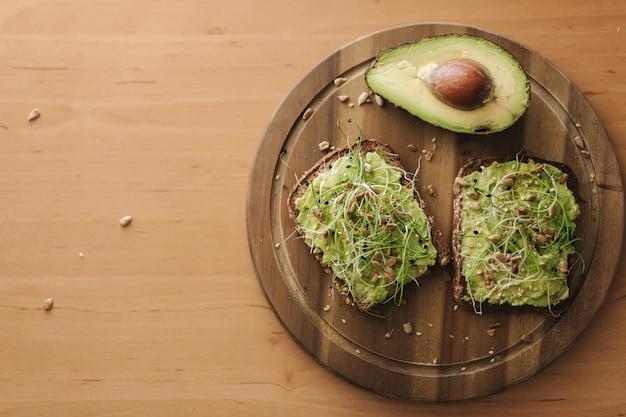 Vista de cima de um delicioso sanduíche vegan com guacamole e micro verdes por cima. metade do abacate com sanduíche na placa de madeira. conceito de comida vegana.