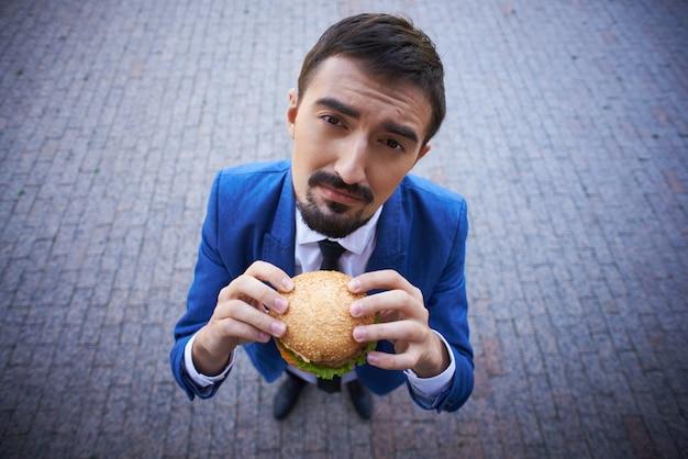 Vista de cima de um empresário com um hambúrguer