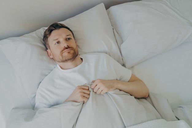 Vista de cima de um jovem barbudo chateado solitário, deitado na cama com os olhos abertos e não consegue dormir, sentindo-se infeliz e cansado, aperta o cobertor com as mãos e está estressado de insônia. problemas para dormir