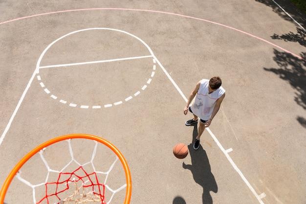 Vista de cima de um jovem jogando basquete, vista de cima aro de um homem driblando o basquete
