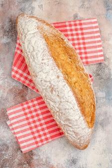 Vista de cima de um pão em uma toalha de cozinha vermelha sobre fundo nu