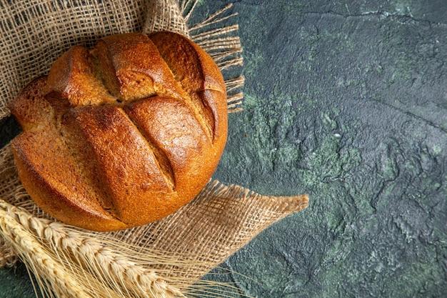 Vista de cima de um pedaço de pão preto dietético em uma toalha marrom em uma superfície de cores escuras