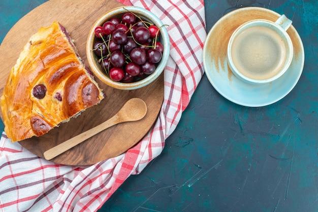Vista de cima de um pedaço de torta de cereja com cerejas frescas em uma mesa azul escura, torta de bolo com frutas doces e açúcar