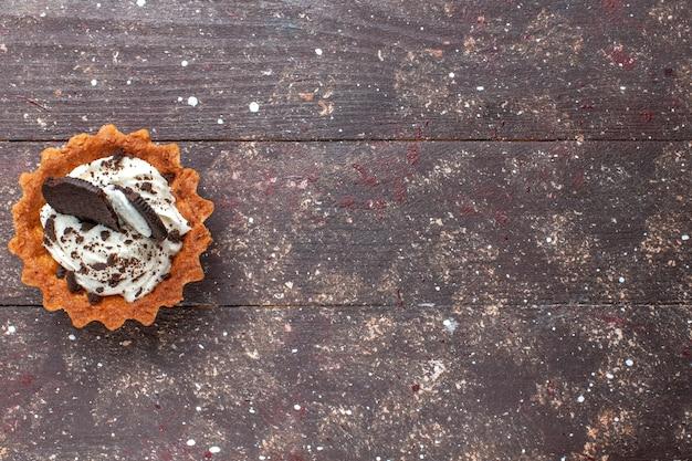 Vista de cima de um pequeno bolo com creme e chocolate isolado em marrom de madeira, biscoito assado
