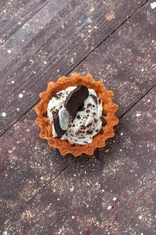 Vista de cima de um pequeno bolo com creme e chocolate isolado em um marrom de madeira, bolo, biscoito, doce, assar