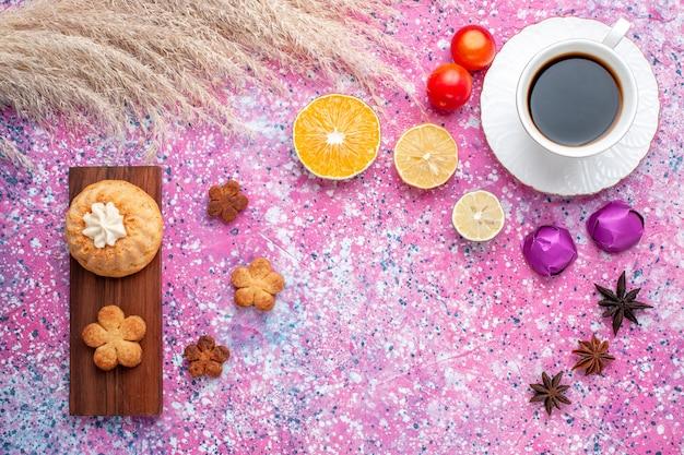 Vista de cima de um pequeno bolo com uma xícara de chá e fatias de laranja na superfície rosa