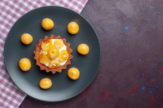 Vista de cima de um pequeno bolo cremoso com cerejas frescas dentro do prato em uma superfície roxa escura