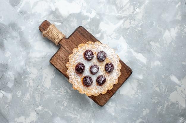 Vista de cima de um pequeno bolo de açúcar em pó com cerejas na mesa leve, bolo de biscoito, café, açúcar, doce
